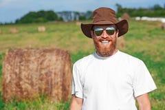 微笑的农夫画象干草领域的 免版税库存照片