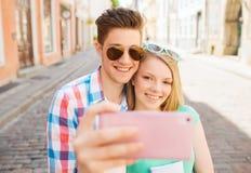 微笑的加上智能手机在城市 免版税库存图片