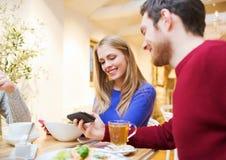 微笑的加上见面在咖啡馆的智能手机 库存照片