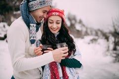 微笑的加上Portrain杯子热的茶在他们的手上在冬天期间走 免版税图库摄影