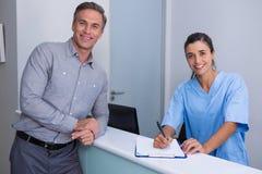 微笑的医生候宰栏支持的人画象书桌的 免版税库存图片