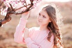 微笑的十几岁的女孩在桃子庭院里 库存图片
