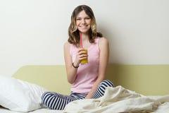 微笑的十几岁的女孩在睡衣的13年,在家坐在床和饮用的橙汁上 库存照片
