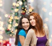 微笑的十几岁的女孩拥抱 免版税库存图片