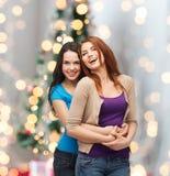 微笑的十几岁的女孩拥抱 免版税库存照片