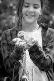 微笑的十几岁的女孩的黑白特写镜头图象在手上的举行成熟白色 免版税库存图片