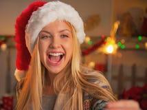 微笑的十几岁的女孩画象拿着闪烁发光物的圣诞老人帽子的 库存图片