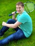 微笑的十几岁的男孩,当拿着网球拍时 库存图片