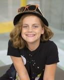 微笑的十岁的女孩坐桌 免版税库存图片