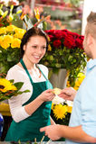 微笑的卖花人人客户采购的花看板卡 免版税库存图片