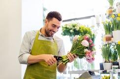 微笑的卖花人供以人员做束在花店 免版税库存照片