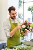 微笑的卖花人供以人员做束在花店 免版税库存图片