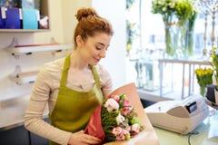 微笑的卖花人妇女包装的束在花店 免版税库存照片