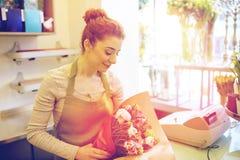 微笑的卖花人妇女包装的束在花店 免版税库存图片