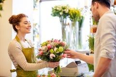 微笑的卖花人妇女和人在花店 库存图片