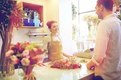 微笑的卖花人妇女和人在花店 库存照片