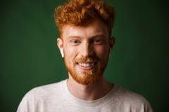 微笑的卷曲红头发人人特写镜头画象,听mus 免版税库存照片