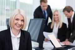 微笑的友好的女实业家在办公室 免版税图库摄影