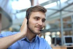 微笑的友好的英俊的年轻男性电话中心操作员 库存图片
