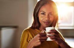 微笑的友好的年轻黑人妇女饮用的咖啡 库存图片