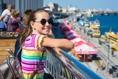 微笑的可爱的女孩少年13, 14岁 背景河堤防,城市,内河港 免版税库存图片