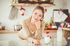 微笑的可爱的妇女吃早餐在厨房内部 微笑的可爱的妇女 免版税库存图片