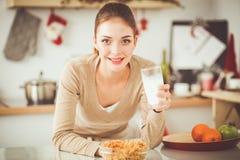 微笑的可爱的妇女吃早餐在厨房内部 微笑的可爱的妇女 库存照片