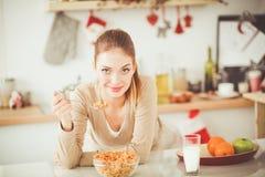 微笑的可爱的妇女吃早餐在厨房内部 微笑的可爱的妇女 免版税库存照片