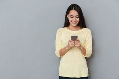 微笑的可爱的少妇身分和使用手机 免版税库存图片