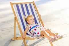 微笑的可爱的blondy女婴画象放松在sunbed的礼服或小孩孩子的或在城市公园recre的一deckchair 免版税库存照片
