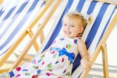微笑的可爱的blondy女婴画象放松在sunbed的礼服或小孩孩子的或在城市公园recre的一deckchair 库存图片