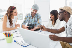 微笑的同事与数字照相机一起使用 免版税图库摄影