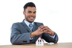 微笑的商人保护的房子模型和汽车用手 免版税库存图片