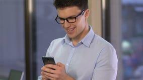 微笑的商人卷动智能手机,读书消息,移动通信 股票视频