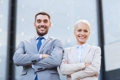 微笑的商人和女实业家户外 免版税库存图片