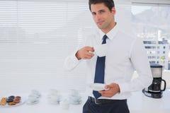 微笑的商人喝咖啡在断裂期间 免版税库存图片