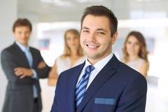 微笑的商人在有同事的办公室在背景中 免版税图库摄影