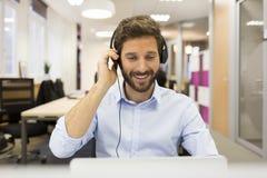 微笑的商人在电视电话会议的办公室,耳机, 库存照片