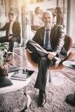 微笑的商人坐椅子在办公室 免版税库存照片