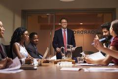 微笑的商人对队演讲在会议,低角度上 库存照片