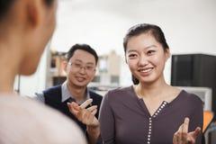 微笑的商人开会议在办公室,谈话 免版税图库摄影