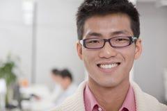 微笑的商人微笑在办公室的,工友在背景中 库存图片
