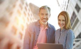 微笑的商人的综合图象和女实业家拿着一台膝上型计算机 免版税图库摄影