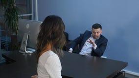 微笑的商人谈话与他的同事在一次非正式会议期间在办公室 免版税库存图片