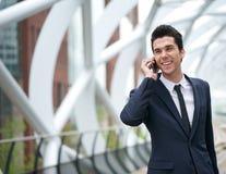微笑的商人谈话在手机在城市 库存图片