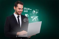 微笑的商人身分和使用膝上型计算机的综合图象 免版税库存图片