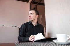 微笑的商人饮用的咖啡和读本文 库存照片