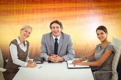 微笑的商人画象的综合图象坐在会议桌上的  免版税库存图片