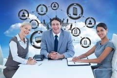 微笑的商人画象的综合图象坐在会议桌上的  免版税图库摄影