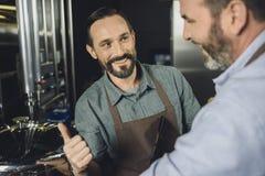 微笑的啤酒厂工作者 免版税图库摄影
